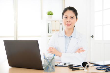 医療事務で働く美しい医師は、オンライン システム思いやりのある人の健康状況をコンピューターとインターネットで彼女の治療患者関係を接続し 写真素材