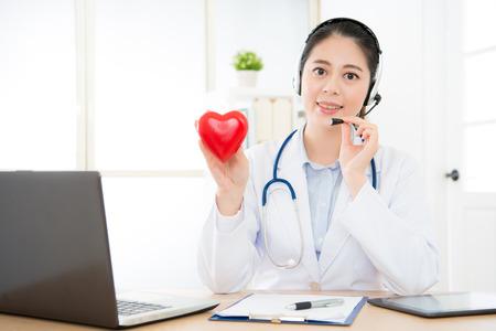 Lächelnde Ärztin, die Kopfhörer zum Gespräch im Klinikbüro mit Kardiologiepatienten unter Verwendung des on-line-Technologie-Service-Systems verwendet. Standard-Bild - 82747038
