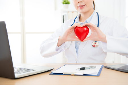 closeup photo of pretty smiling female doctor using online service for cardiology patient and showing heart model on working desk.
