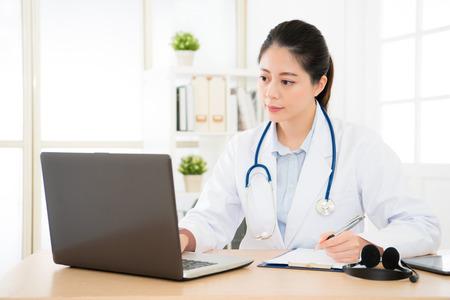 真剣にオンライン医学システムによる新しい患者のカルテを検索、紙基板研究治療法に関するメモを書く専門の医者。