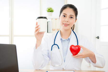 smiling young female cardiology doctor face to camera on working desk and holding coffee cup showing caffeine causing palpitations problem concept. Stock Photo