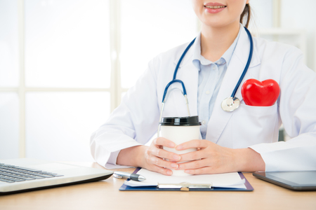 closeup photo of professional smiling doctor woman holding coffee cup working on cardiology office and offers online service for patient advisory palpitations problem.