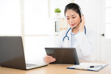 arts die met zieke persoon door laptop online systeem spreekt en mobiele digitale tabletcomputer gebruikt die geduldige medische verslagen op het document van gegevensbestandbestanden zoekt.