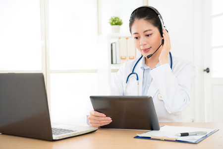 doctor talking with sick person through laptop online system and using mobile digital tablet computer searching patient medical records on the database files document.