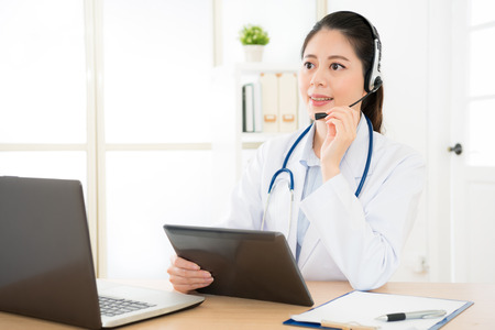 online service female doctor provide the most appropriate medical information for calling patient with laptop computer and mobile digital tablet pad record talking content. Banco de Imagens
