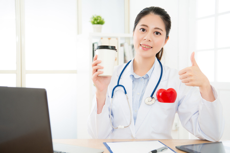 beautiful attractive woman rights cardiology doctor holding coffee cup looking at camera and showing thumb up gesture when she working on office.