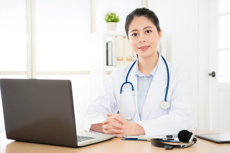 friendly doctor with stethoscope in front of modern laptop in her clinical office giving service for patient, shot of frontal view and medical consultation online concept. Stock Photo