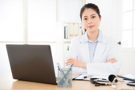 zekere vrouwelijke artsenzitting bij bureau die alle geduldige gemak online dienst geven en met gekruiste handen, gezondheidszorg en het concept van de preventieziekte glimlachen.
