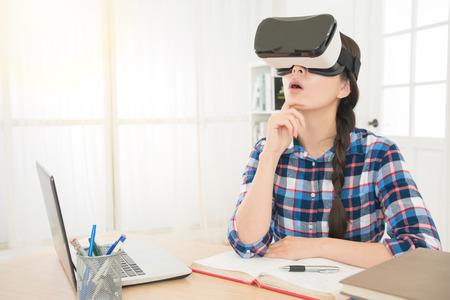 仮想現実を身に着けている質問について考える混血アジア女感じて驚いて VR デバイス 3 d イメージ ビデオを表示する office 職場で座ってをゴーグル