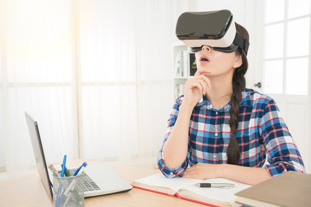 mixed race asian woman thinking about question wearing virtual reality goggles sitting at office workplace viewing VR device 3d image video feeling surprised. Stok Fotoğraf