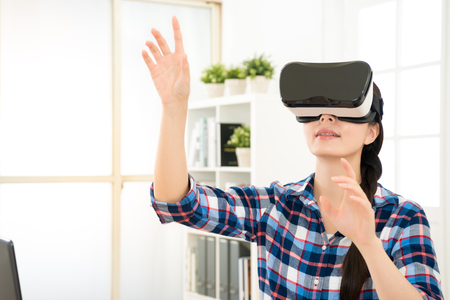 close up of smile happy woman getting using VR-headset glasses of virtual reality at home and showing much gesticulating hands as organize image on the video. Imagens