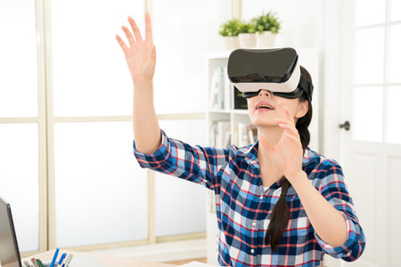 asia beautiful student organize class content by virtual reality in air. person wearing VR headset interact with fictitious image moving with hands raise.
