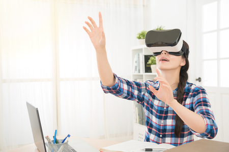 woman in virtual reality headset looking up and trying to touch objects with computer technology simulates a video presence and let the user to interact on air.