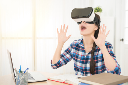 attractive shocked woman enjoying virtual reality glasses in modern interior design studio play online with VR goggles headset feeling surprised opened mouth and reflect exaggerated.