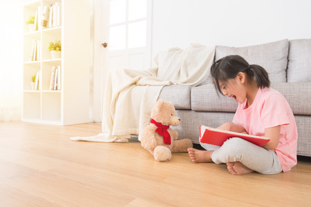 beautiful female children with teddy bear sitting on wooden floor and watching new toy book happily in the holiday afternoon playing in front of living room sofa.