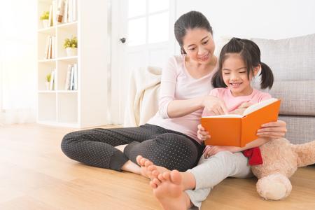 母と子、女の子とテディベアの家の木製の床のリビング ルームに座っている喜びを共有するための写真のコンテンツを指す休日に家族のアルバムを読みます。 写真素材 - 83059096
