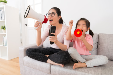 young mom and daughter through megaphone watching the sports channel broadcast sports game to help support the team cheer up hope to win the game win at home on the couch.