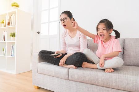 少女見て興奮して試合に勝つお気に入りのチームと、mom サポート チームが信じられないほどスポーツ ゲーム チャンネルを見てソファに一緒に座ってを失っていたことを学んだ。 写真素材 - 83059099