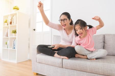 テレビのスポーツ チャンネルの好きなサッカー チームの勝利を見て子供を持つ幸せな女性は、家族のラウンジのソファの上の勝利を祝うために手拳 写真素材