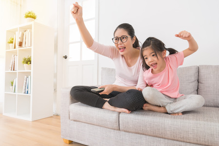happy woman with children watching TV sports channel favorite football team winning was excited to hands fist gesture to celebrate victory on the sofa in the family lounge. Stok Fotoğraf