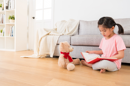 portrait of girl and her teddy bear seriously study at home and reading the favorite story book to share with each other to enjoy the summer vacation with the best friend. Stock fotó