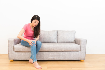joven y bella mujer sentía dolor de rodilla después de un movimiento deportivo se lesionó sentado en el sofá en la sala de estar a descansar en el suelo de madera con fondo blanco.