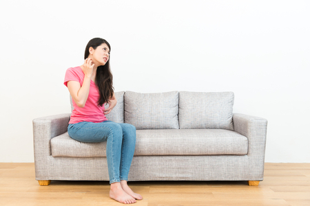 young attractive woman having allergy problem feeling body itchy sitting on sofa and looking at white background using hand scratching to soothing in wooden floor. Banque d'images