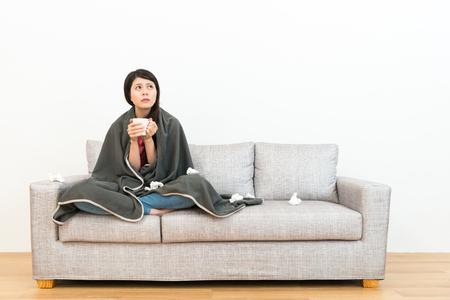 piękne ładne kobiece teenger łapanie zimny siedzi na kanapie kanapie i trzymając kubek gorącej filiżanki patrząc na białym tle myślenia rozwiązanie z drewnianą podłogą.