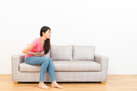 young woman sitting on couch sofa making stomach pain gesture and feeling uncomfortable in the wooden floor with white background.