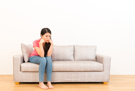 슬픈 외로운 여자 우울한 흰 벽 배경 copyspace 통해 나무 바닥 거실에 소파에 앉아 가족 어려움에 대 한 문제에 [NULL]에 대해 생각합니다.