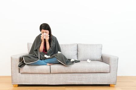 młoda piękna kobieta siedzi na kanapie kanapie w drewnianej podłodze i przy użyciu bibuły dmuchanie nos pochlipywania, gdy ona łapie przeziębienie z białym tłem.
