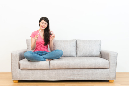 young sweet woman holding donuts and toothbrush sitting on sofa looking at camera showing teeth cleaning concept with white background. Stock Photo - 83093423