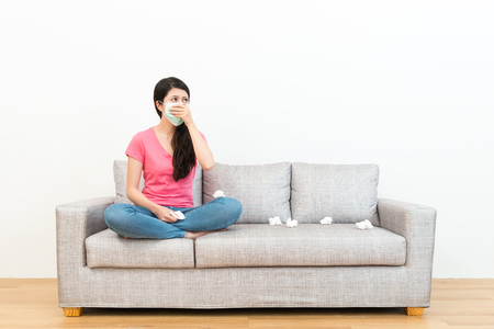 elegant lovely woman sitting on sofa couch wearing medical mask and looking at white background thinking solution when she coughing. Foto de archivo