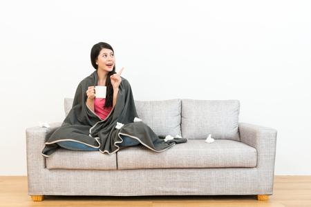 szczęśliwa piękna studentka wskazując białe tło i trzymając gorący kubek siedzi na kanapie w drewnianej podłodze, gdy ona łapie przeziębienie. Zdjęcie Seryjne