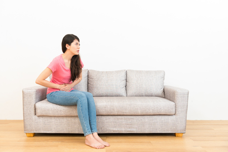 young woman in menstrual period feeling uncomfortable and abdominal pain unhappy sitting on couch resting on wooden floor.