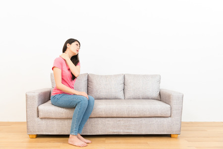 back ache: woman sitting long time working feeling shoulder and neck pain stretching on sofa soothing painful with white background on wooden floor.