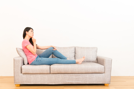 asian chinese female student sitting on the living room sofa worry about future planning ideas about work or study on the copyspace with white background in the wood floor.