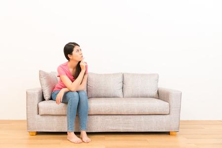 여자 찾고 소파에 앉아 흰 벽 배경 가진 나무 바닥에 포즈를 생각합니다.