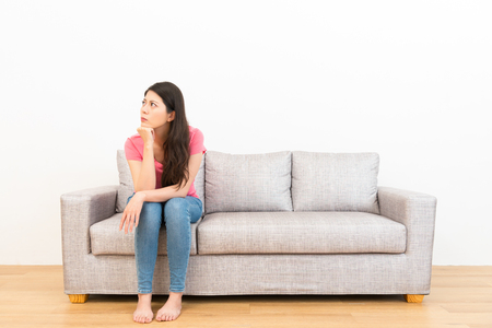 serious woman angry back to white background sitting on couch sofa in wooden floor on leisurely afternoon daze day dreaming at home.