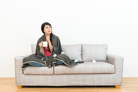 unhappy pretty lady catching a cold feeling throat painful drinking hot water and sitting on sofa couch looking at white background with wooden floor.