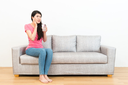 sweet lovely woman put her hands in uncomfortable position after drinking ice water feeling sensitive tooth painful and sitting on sofa looking at white background.