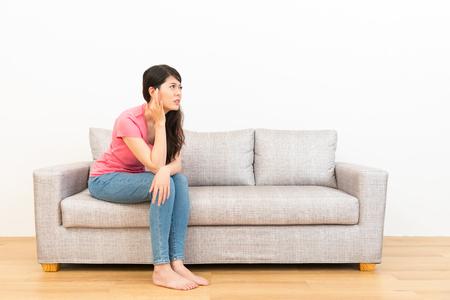 若い女性は、自宅のリビング ルームで木製の床と白い背景を見てソファに座って耳の痛みを伴う位置を粉砕しました。 写真素材