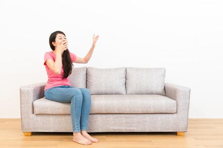 피곤 여자 하품 피곤 하 고 흰 벽 배경 가진 나무 바닥에 거실에 소파에 앉아 제스처를 중지합니다.