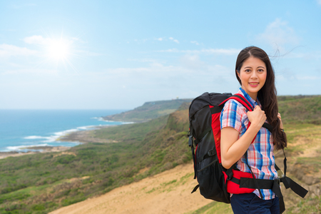 female climber woman carrying hiking backpack standing at the highest point of the mountain back to the coastal landscape in the sunny morning holiday at Beinn Alligin, Wester Ross, Scotland. Stock Photo