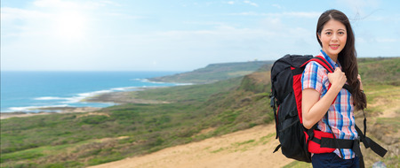 female climber woman carrying hiking backpack standing at the highest point of the mountain back to the coastal landscape in the sunny morning holiday with banner crop for copy space.
