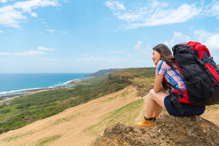 successful trekking traveler sitting on hill top to resting relax enjoying ocean scenery with green coast happy look at the sky. Imagens