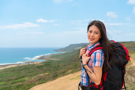 beautiful asian hiker carrying a backpack going to the famous island country hiking at the highest point with the ocean mountain background taking pictures with copyspace. Stock Photo