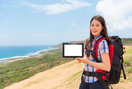 female backpacker showing mobile pad computer blank screen in hands standing on hiking mountain with coastal background.