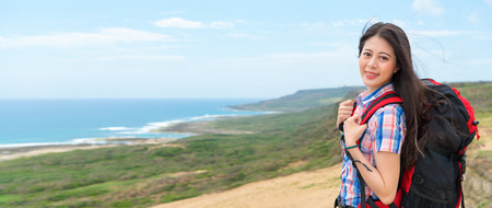 beautiful asian hiker carrying a backpack going to the famous island country hiking at the highest point with the ocean mountain with banner crop for copy space.