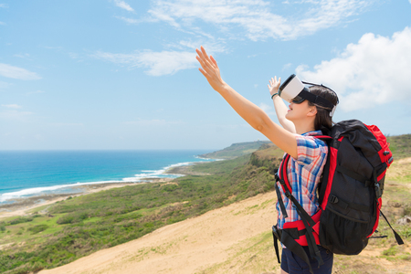 happy woman hiker wearing a virtual reality device through 3D images enjoy the immediate coastal scenery and raised her hands experience the sea breeze with blank copyspace.